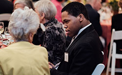 Jazz piano student Isaiah Thompson speaking with an attendee.